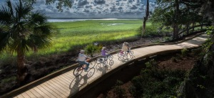 3 bikers on boardwalk with marsh. Photo-Jekyll Island Authority